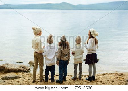 Group of little buddies standing by water