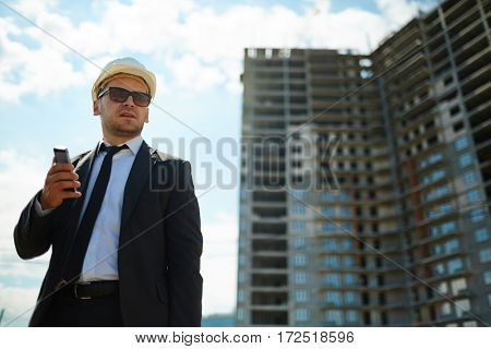 Portrait of successful confident businessman wearing hard hat and sunglasses with black suit standing looking away against high-rise apartment building under construction