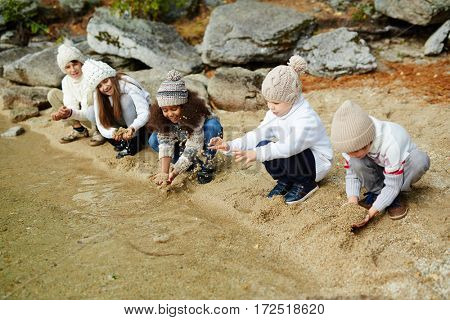 Group of kids playing by water on sand
