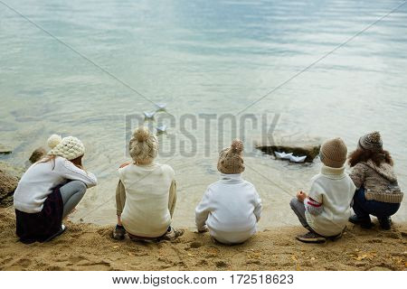 Rear view of several youngsters looking at paper-boats on water