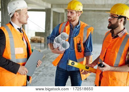 Group of three workmen wearing protective helmets and vests standing among concrete walls on construction site discussing development progress with inspector, holding tools and blueprints