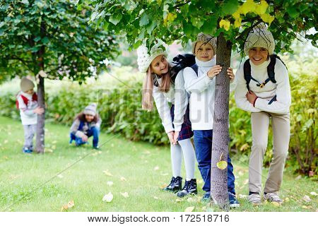 Group of friendly kids standing under linden tree