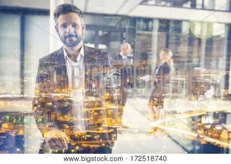 Portrait of businessman standing in office corridor and colleagues talking in background