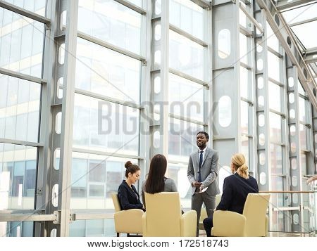 Young employees listening to their business leader