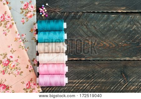 Fabrics spools of thread and pins on old wooden background. Sewing accessories. Top view