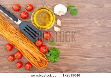 Cherry tomatoes pasta olive oil garlic herbs and pasta tongs on the old wooden background. Rustic style. Traditional Italian food. Selective focus