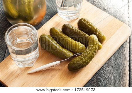 Pickled cucumbers and shot glass of vodka on wooden background. Rustic style