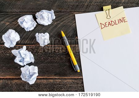 Sticky note with the word deadline. White blank paper crumpled paper and pen on a wooden background
