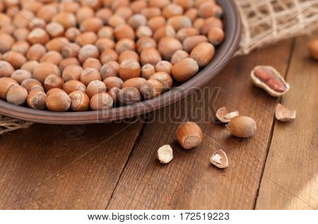 Hazelnuts on a plate and peanut pods kernel hazelnut on wooden brown background. Selective focus