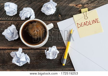Sticky note with the word deadline. White blank paper crumpled pape pen and a cup of coffee on a wooden background