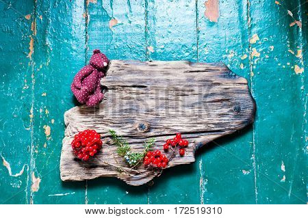 Old wooden board decorated with fir branches and red berries as a background or frame for text for Christmas