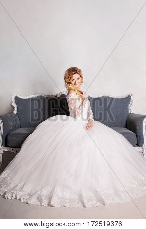 Portrait of charming woman in a wedding dress. The girl bride sits in a chair
