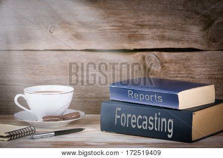 Forecasting and Reports. Stack of books on wooden desk.