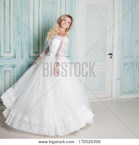 Portrait of charming woman in wedding dress. Dancing on the background walls