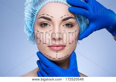Gorgeous girl with dark eyebrows and nude make up at blue background, doctor's hands in blue gloves touching patient's face, plastic surgery, perforation lines on face.