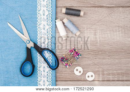 Jeans fabric for sewing lace and accessories for needlework on old wooden background. Spool of thread scissors buttons sewing supplies. Set for needlework top view