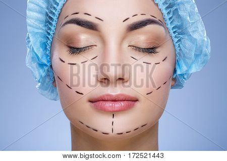 Nice girl with dark eyebrows and naked shoulders wearing blue medical hat at blue background, closed eyes, plastic surgery, copy space, perforation lines on face.