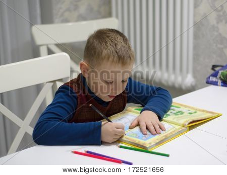 boy sitting at a table and reading a book
