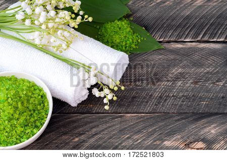 Natural green sea salt and towel for bath and spa on a wooden board. Lilies of the valley in the background. Selective focus