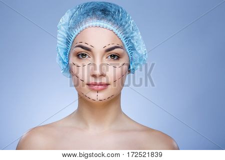 Pretty girl with dark eyebrows and naked shoulders wearing blue medical hat at blue background and looking at camera, plastic surgery, copy space, perforation lines on face.
