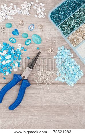 Tools for making jewellery. Crystals pendants charms plier glass hearts box with beads and accessories on old wooden background. Top view