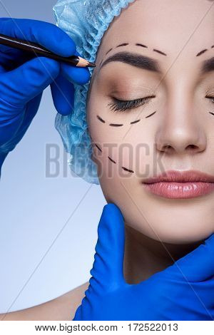 Young  girl with dark eyebrows and nude make up wearing blue medical hat at blue background, doctor's hand making marks on patient's face, perforation lines on face.