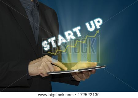 businessman hand holding tablet with a message start up. new business concept.