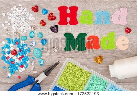 Crystals pendants charms plier glass hearts box with beads accessories to create hand made jewelry and word handmade of felt on wooden background. Tools for creating jewelry