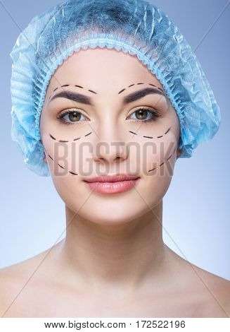 Perfect girl with dark eyebrows and naked shoulders wearing blue medical hat at blue background and looking at camera, plastic surgery, portrait, perforation lines on face.