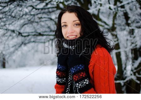 Pretty girl in warm earmuffs blow snow from her hands.Winter clothing, good cold weather.Attractive female model have fun in snowy park at day.Beautiful young chick playing outside in December