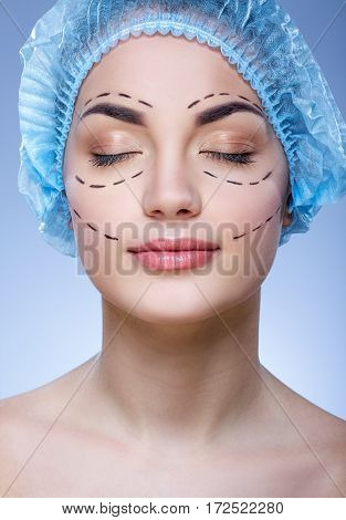 Nice girl with dark eyebrows and naked shoulders wearing blue medical hat at blue background, closed eyes, plastic surgery, portrait, perforation lines on face.