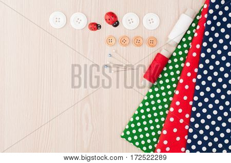 Polka dot fabric for sewing and accessories for needlework on wooden background. Spool of thread buttons sewing supplies. Set for needlework top view