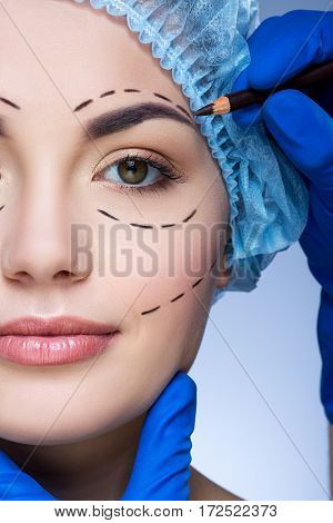Beautiful girl with dark eyebrows and nude make up wearing blue medical hat at blue background, doctor's hand making marks on patient's face, perforation lines on face.