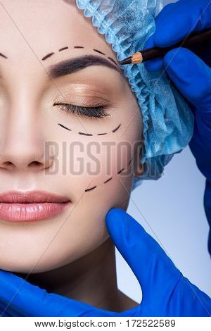 Cute girl with dark eyebrows and nude make up wearing blue medical hat at blue background, doctor's hand making marks on patient's face, perforation lines on face.