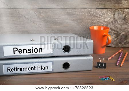 Retirement Plan and Pension - two folders on wooden office desk.
