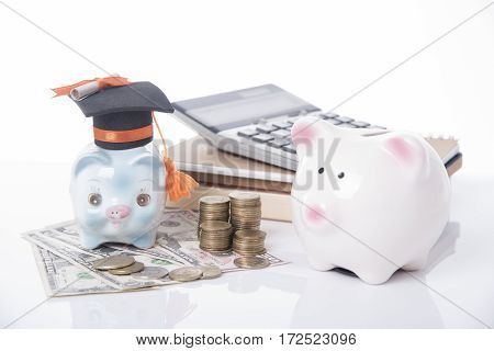 piggy bank and black graduation hat with money book on white table. business finance concept.