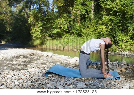 Young beautiful woman meditating near the mountain river. Yoga practicing outdoors.