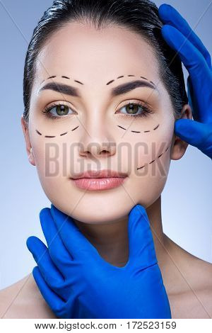 Close up portrait girl with dark eyebrows and nude make up at blue background, doctor's hands in blue gloves touching patient's face, perforation lines on face.