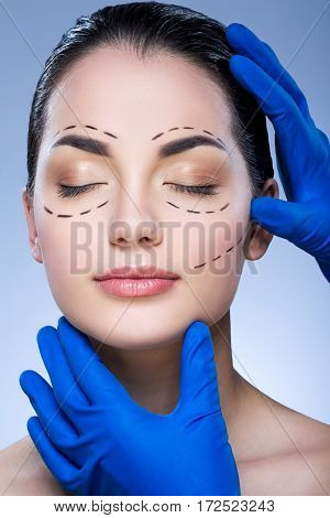 Young  girl with dark eyebrows and nude make up at blue background, doctor's hands in blue gloves touching patient's face, plastic surgery, perforation lines on face.