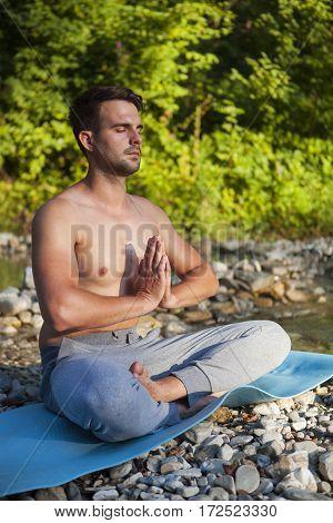 Man Meditating Near The Mountain River. Yoga Practicing Outdoors.