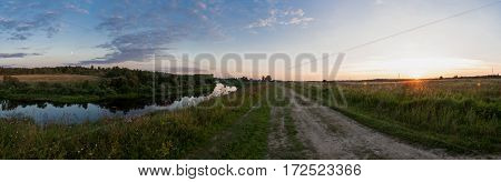 Rural landscape, sunset. The road stretches into the distance, the river on the left side. Shirov panoramma