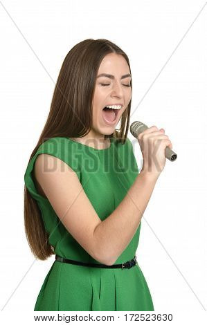 Happy young woman with microphone on white background