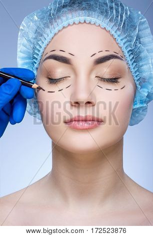 Gorgeous girl with dark eyebrows and naked shoulders wearing blue medical hat at blue background, doctor's hand making marks on patient's face, perforation lines.