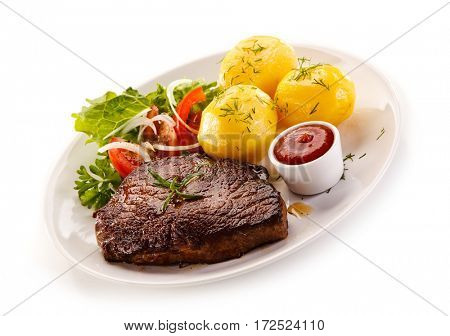 Grilled steaks, boiled potatoes and vegetable salad on white background
