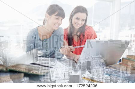 The girls are both sitting beside each other and smiling as they use the laptop as one girl points