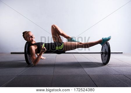 Young woman bench pressing weights at gym, low key