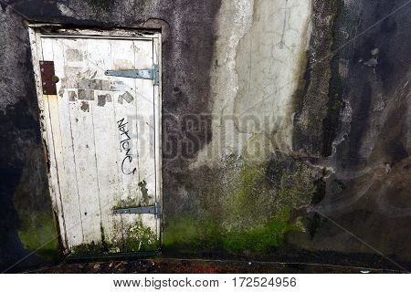 Old white door in a damp rendered wall
