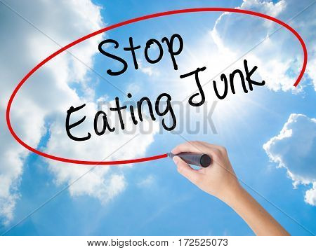 Woman Hand Writing Stop Eating Junk With Black Marker On Visual Screen.