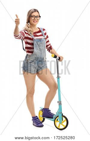 Full length portrait of a female hipster with a scooter making a thumb up gesture isolated on white background