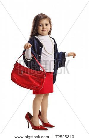 Full length portrait of a little girl in oversized high heels holding a handbag isolated on white background